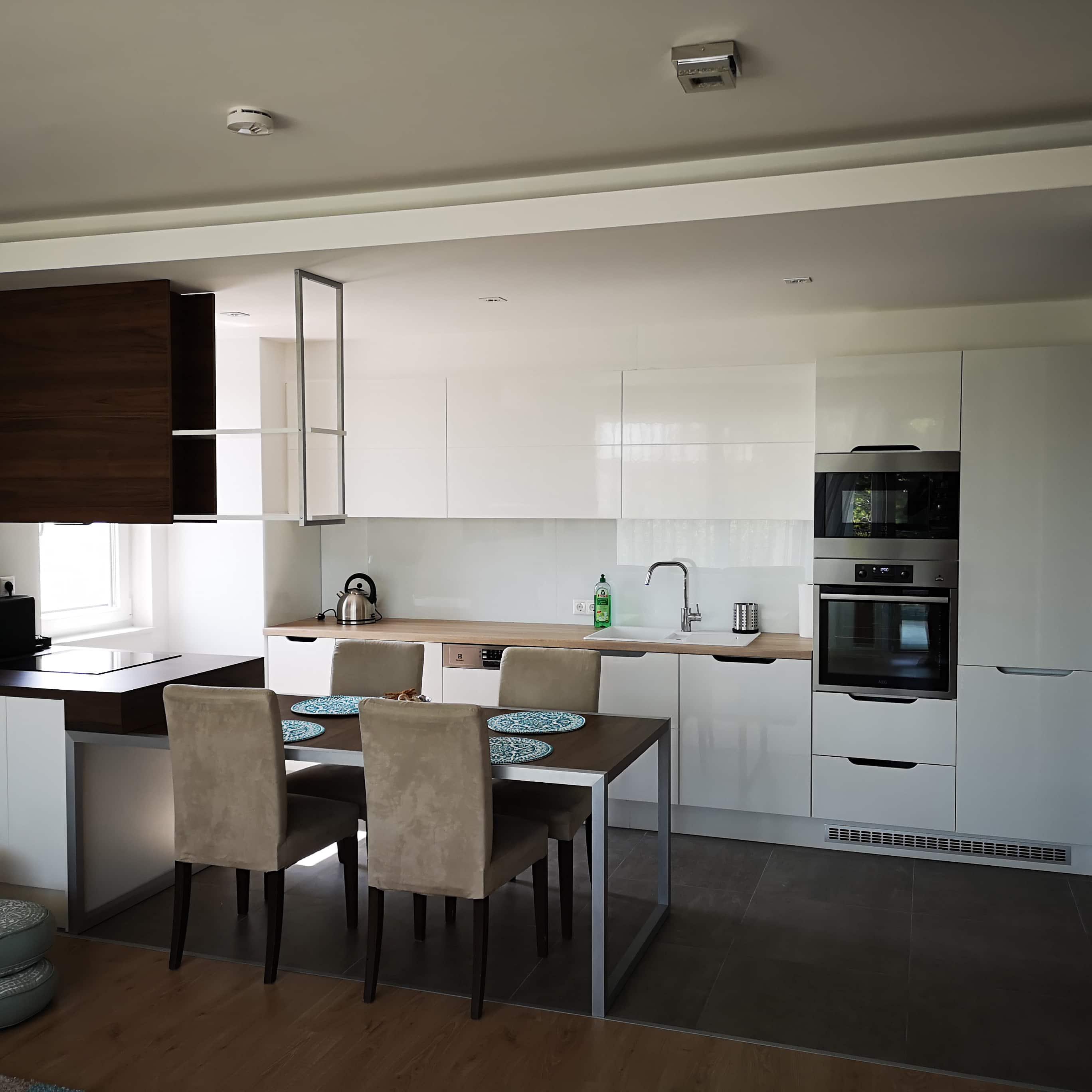Konyha integrált asztallal - magasfényű fehér ajtók , fogantyú kivágással